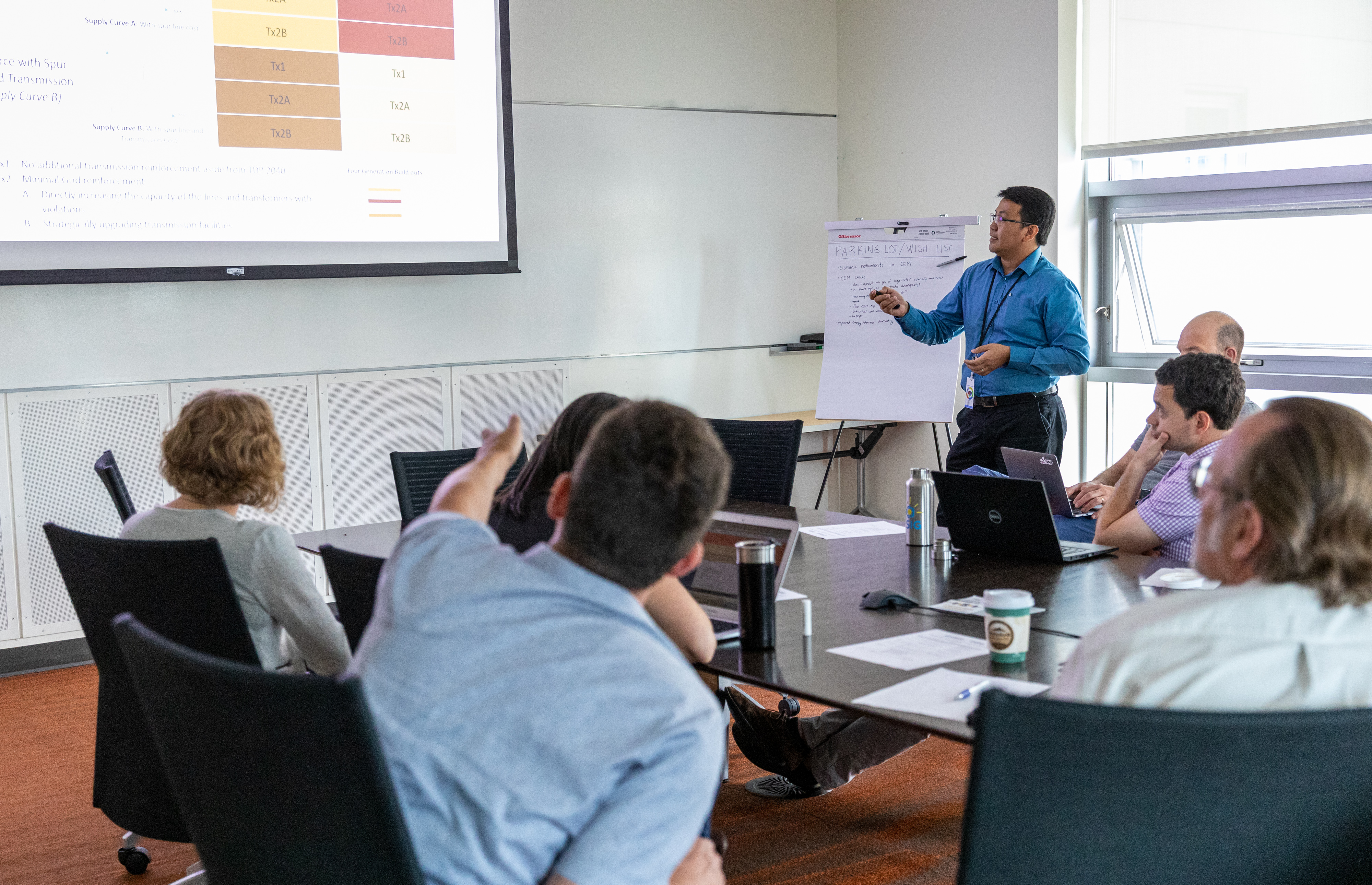 A man presents a PowerPoint slide in front of a group of people.