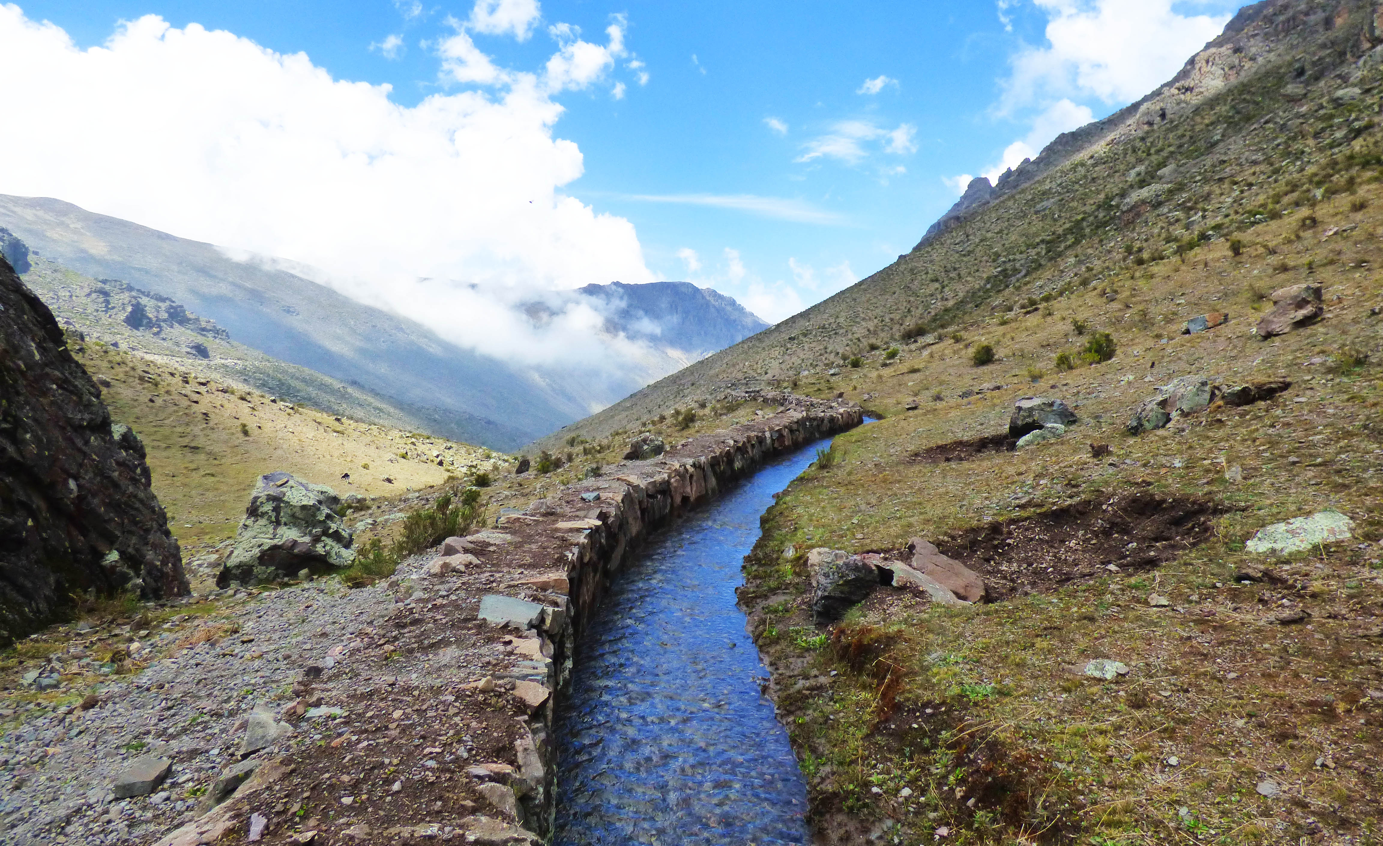 A water canal runs along a mountainside, from the background directly to the camera.
