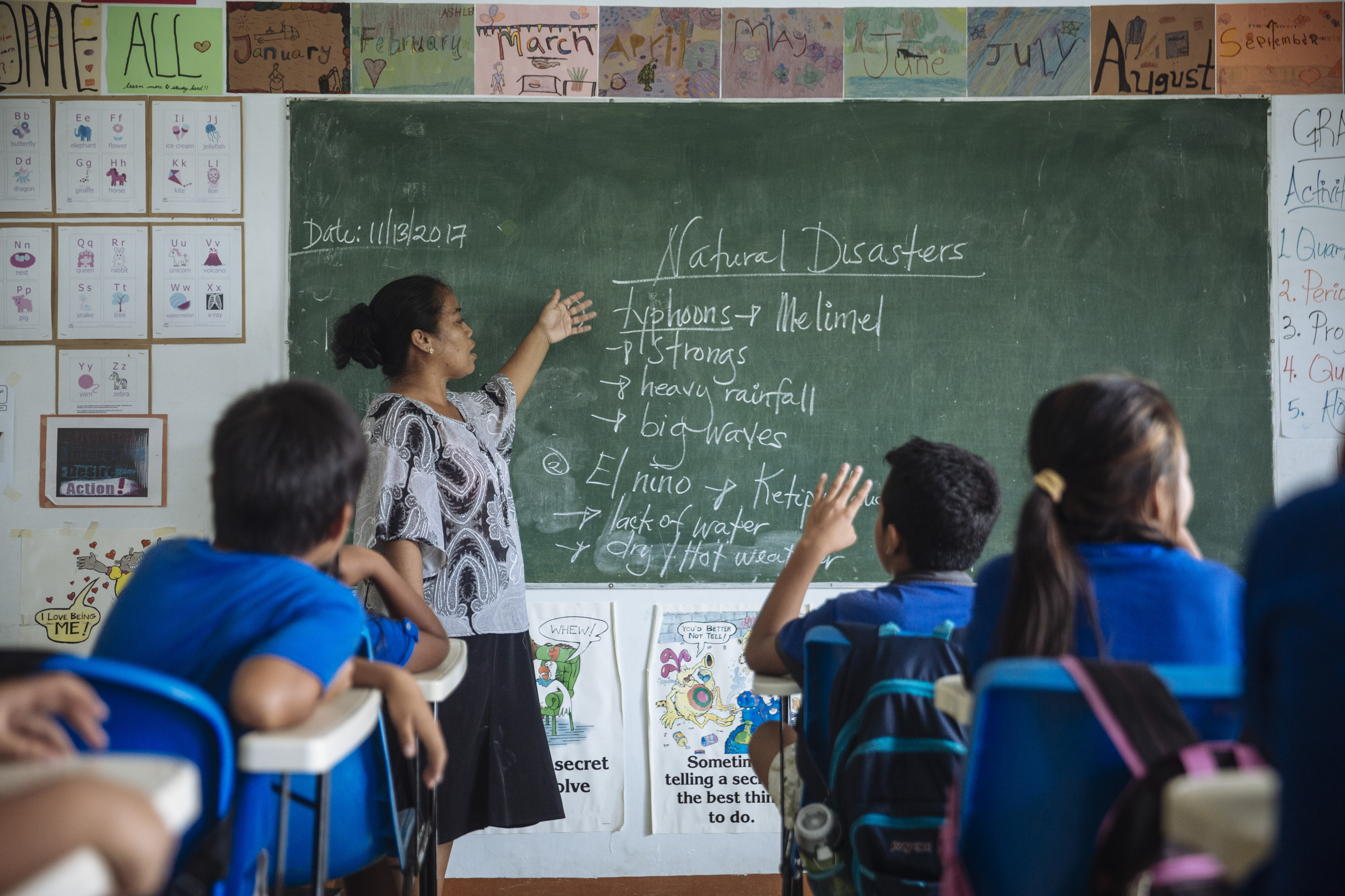 A female teacher leads a class of young students on the topic of natural disasters.