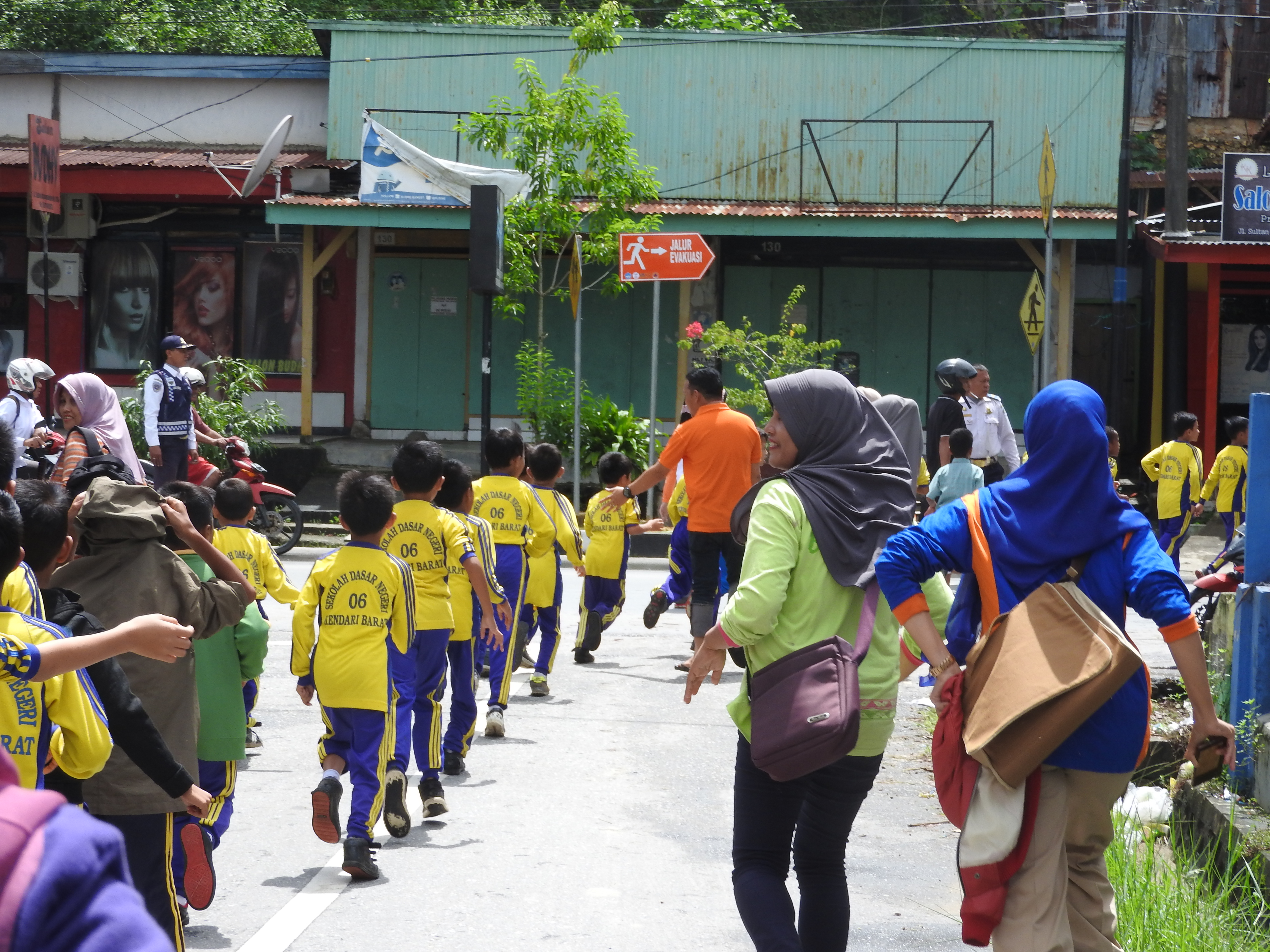 Children line up outside of a school after a disaster evacuation drill.