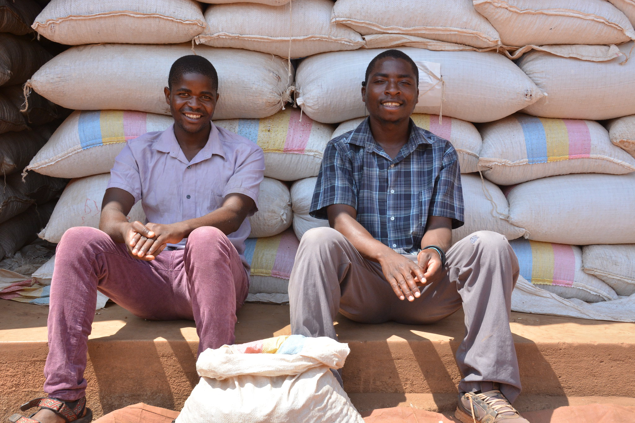 Two men sit in front of a stack of large grain bags, grinning at the camera.