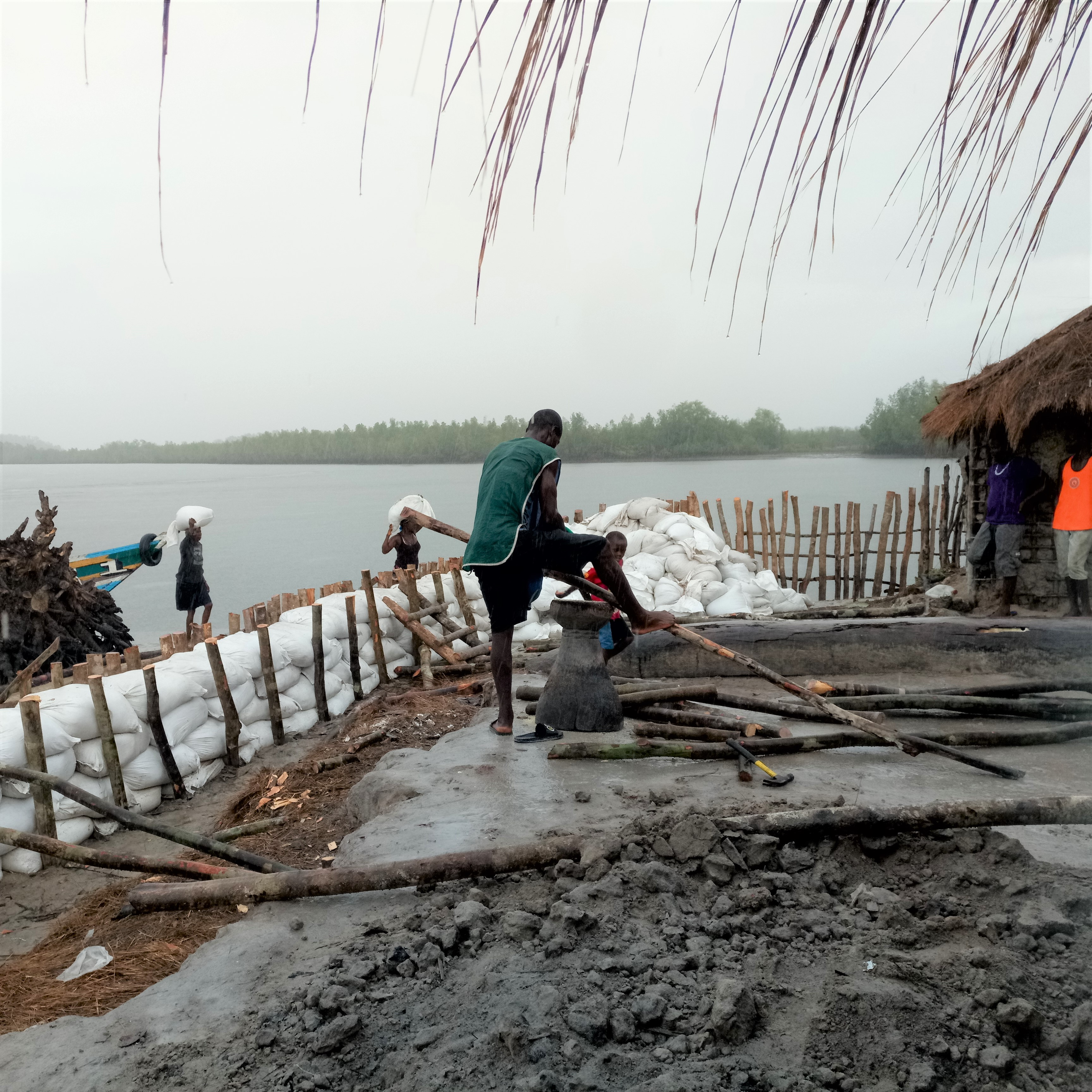Man and other community members use discarded oyster shells, sand bags, and stakes to build embankments along the coast.