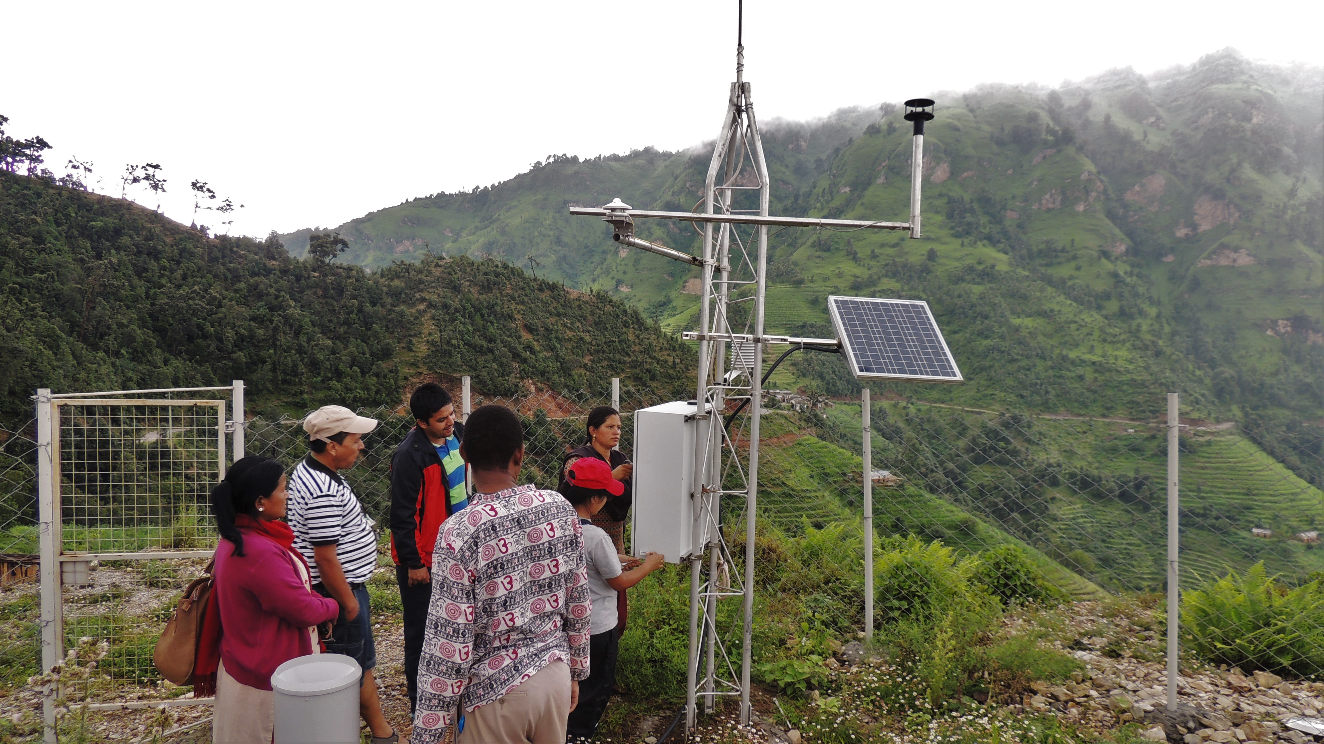 A group of people gather around the bottom of a weather station located on the slopes of a mountain.