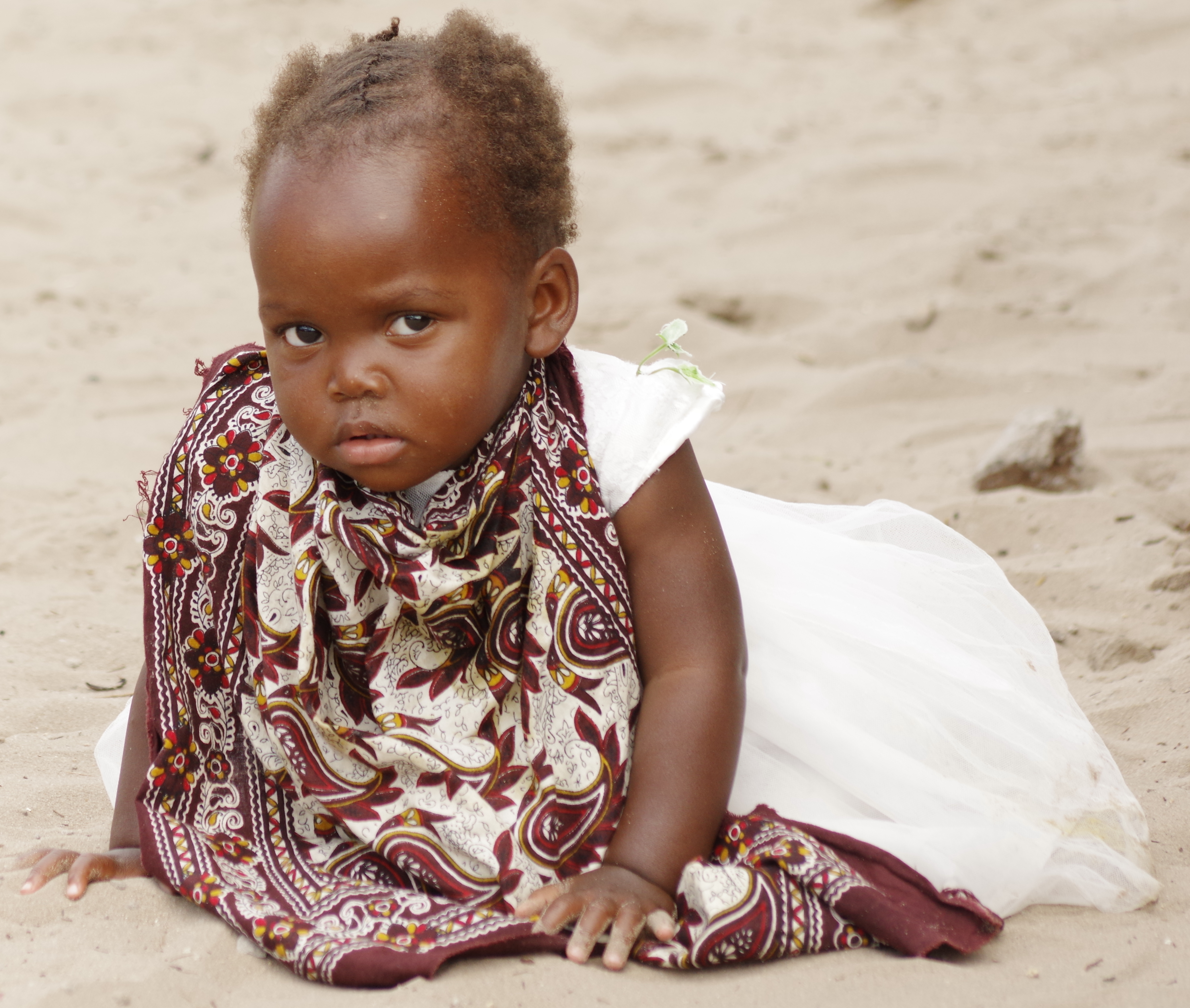 Small girl sitting on sandy ground and looking at the camera.