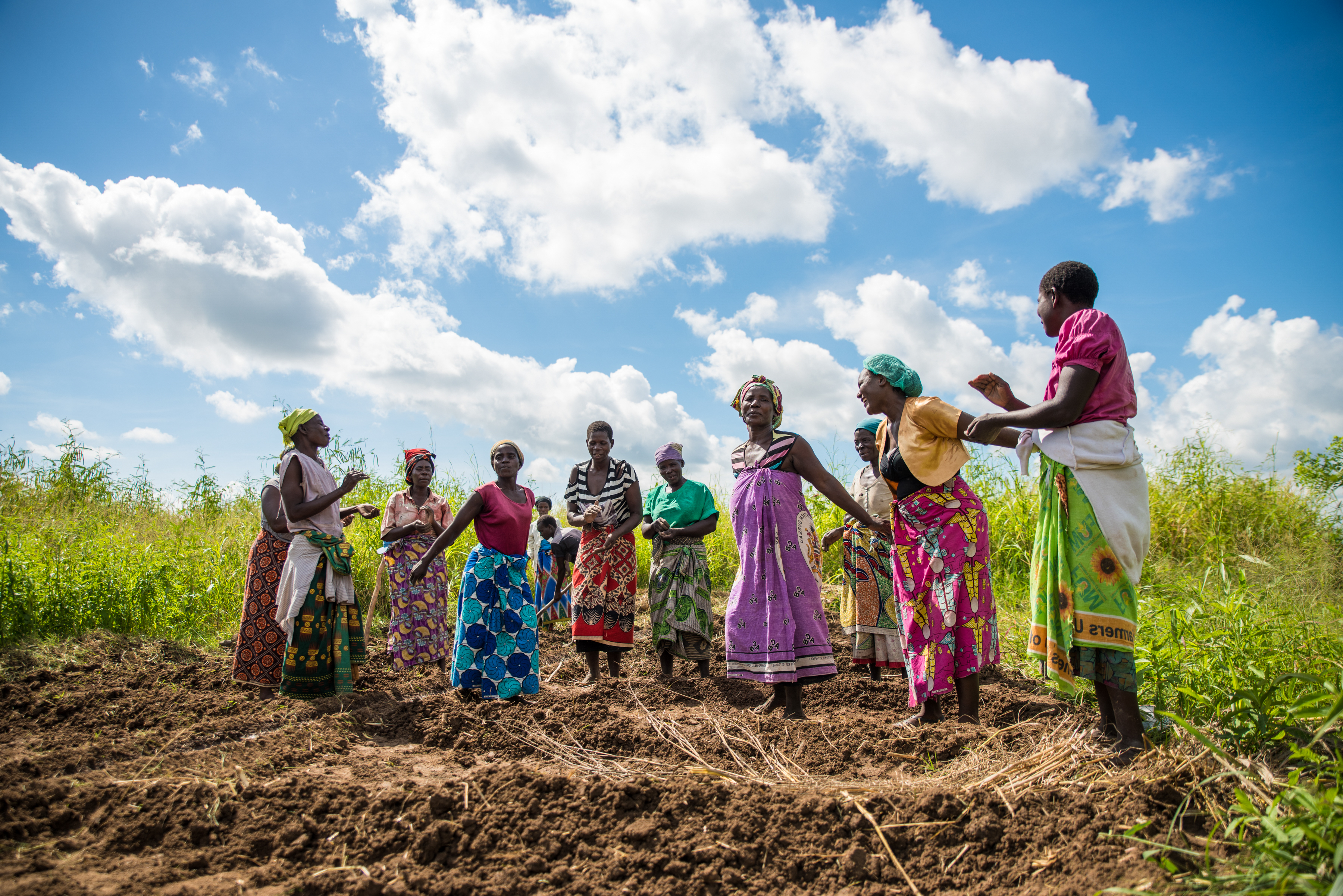 A group of women in colorful clothes stand together on recently tilled land.