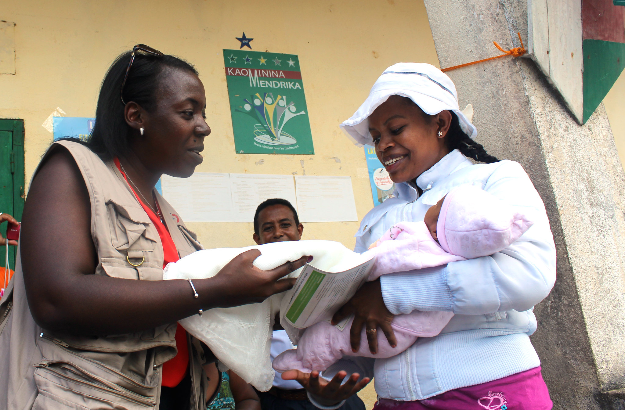 Woman in Madagascar takes a folded mosquito net from a health care worker.