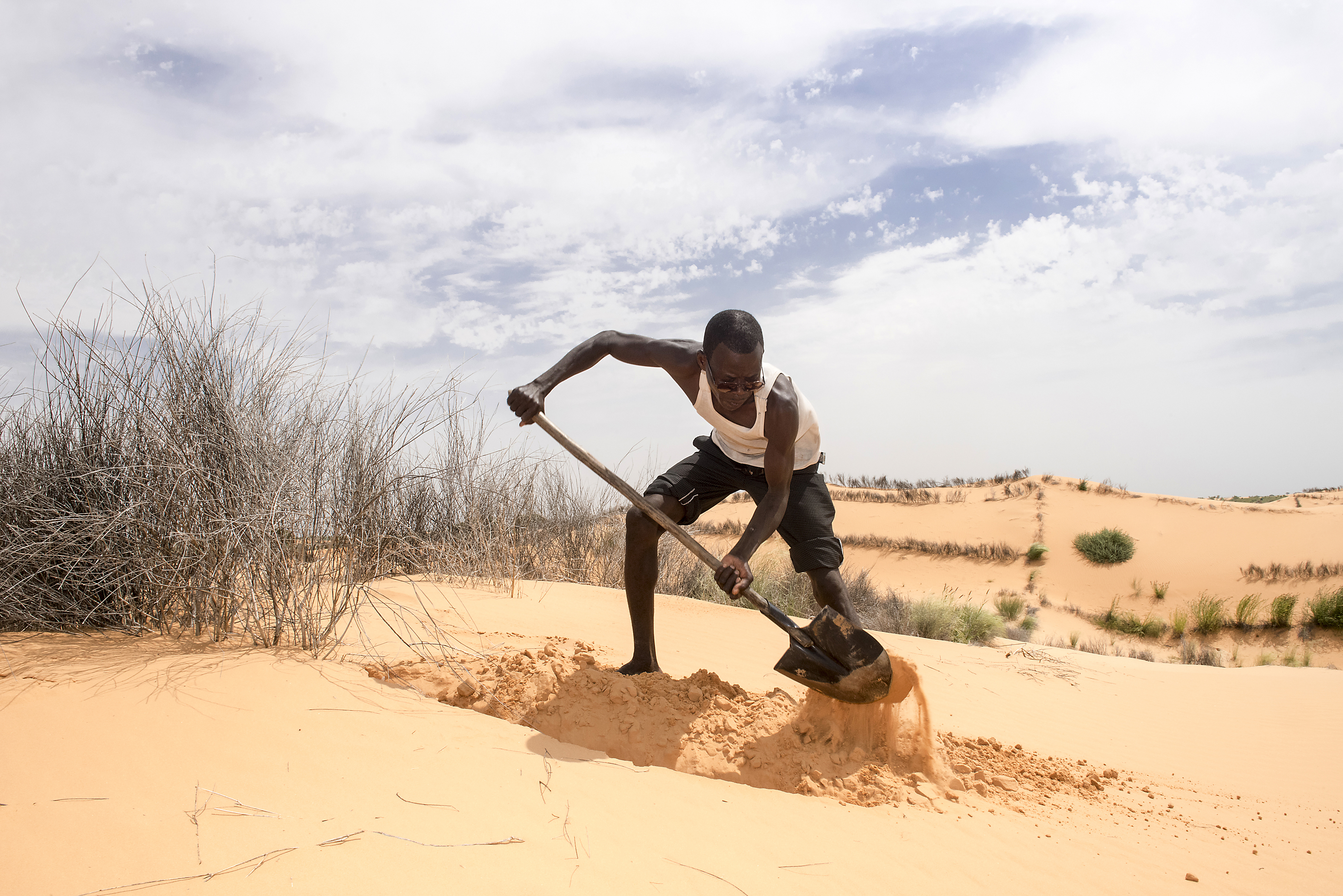 A man shovels sand in a desert area with sand dunes visible in the background.