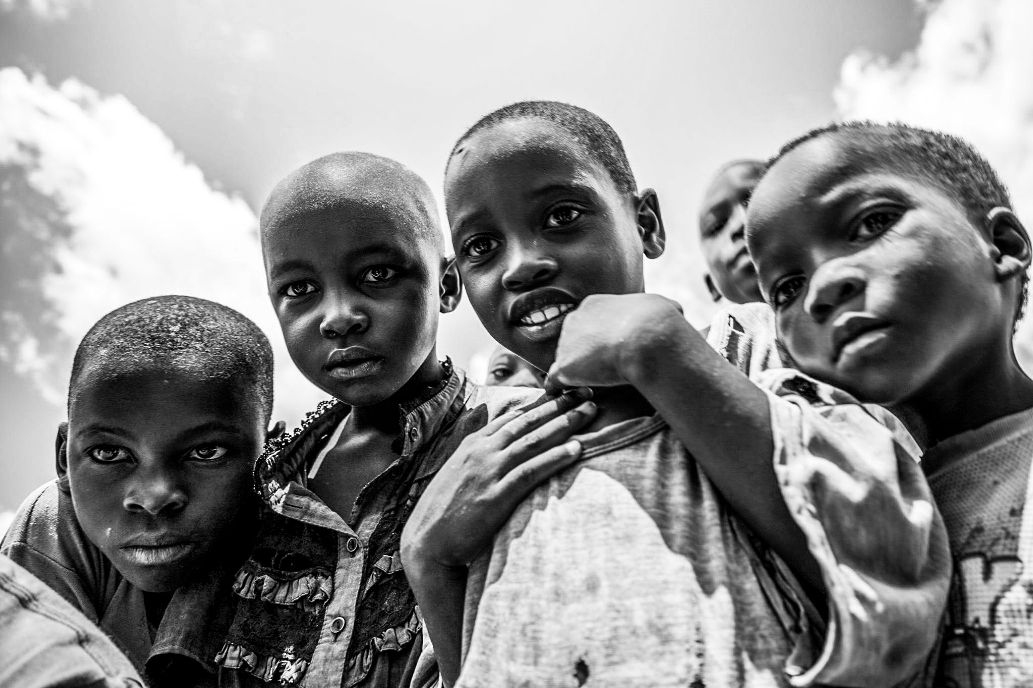 Children looking at a the camera with sky behind them.