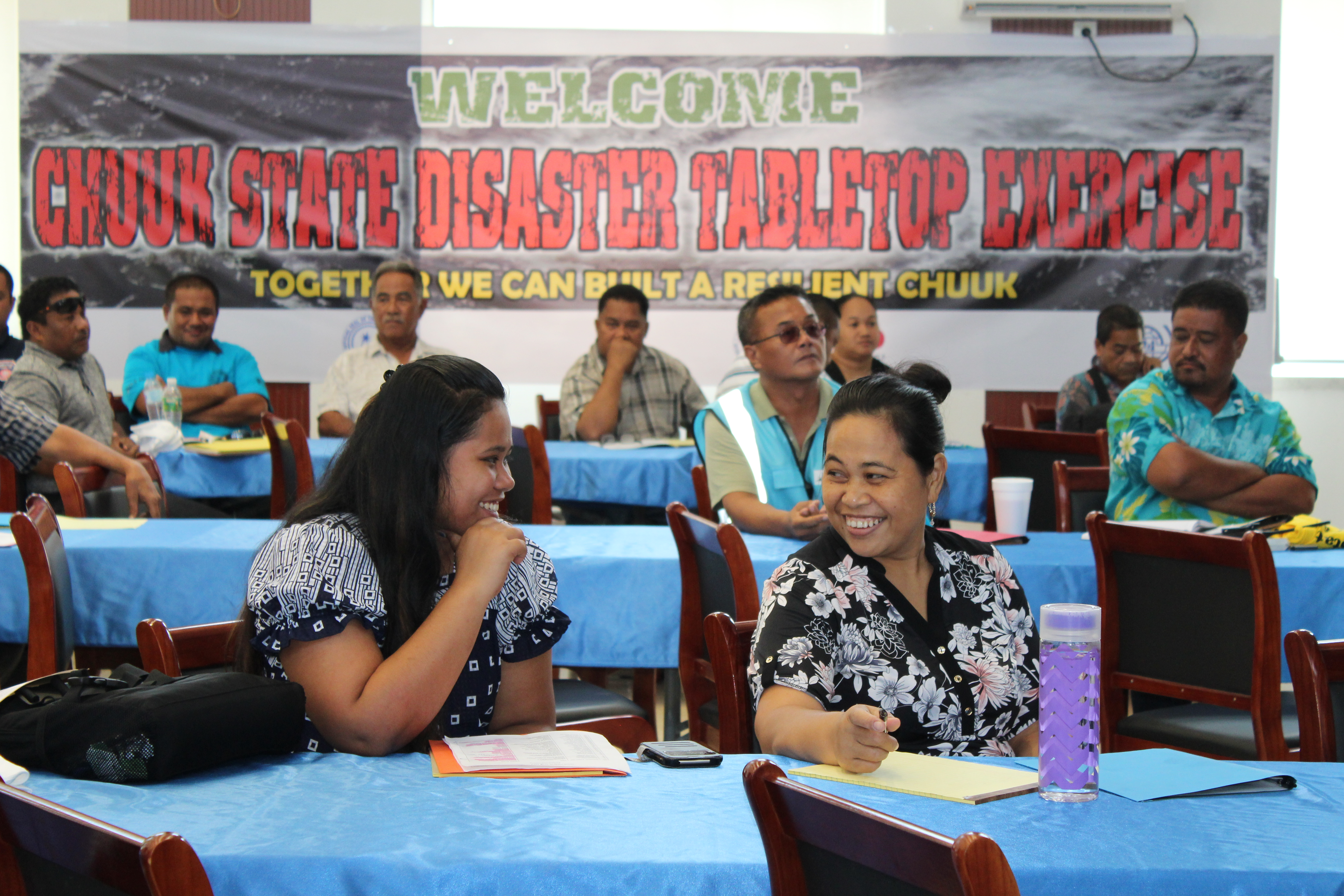 In the foreground, two women sit talking and laughing. A sign behind says 'Chuuk State Disaster Tabletop Exercise.'