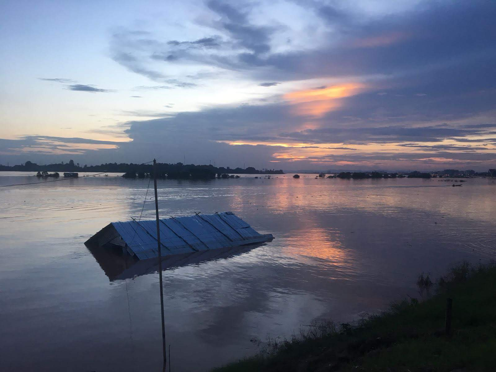 A building submerged in flood waters at dusk.