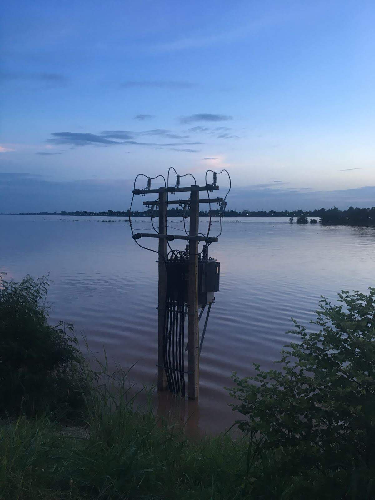 A power distribution line in a flood zone at dusk.