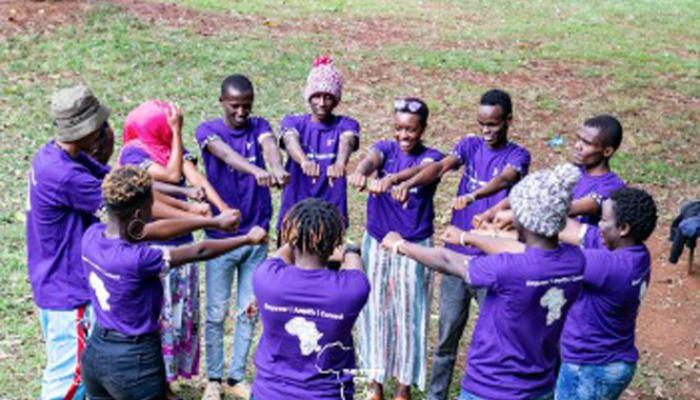 A group of young men and women wearing purple t-shirts stand in a circle and put their outstretched fists together.