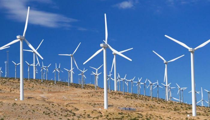 Image of a hillside with numerous white wind turbines standing against a bright blue sky.