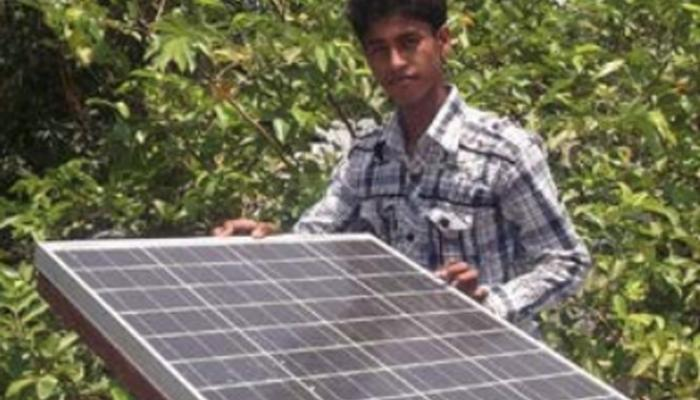 A man holds a solar panel and looks at the camera.