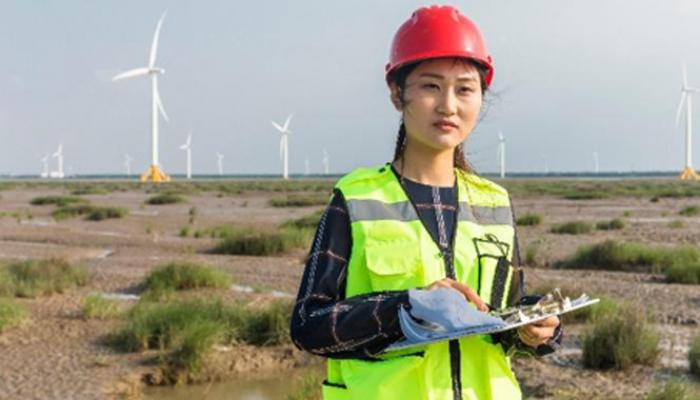 A woman in hi-viz and a hard hat stands on a flat plain with wind turbines in the background.