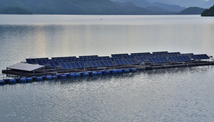A floating solar plant sits on top of a lake in a mountainous region.