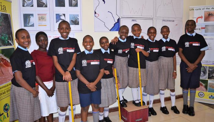 A group of students stands in a classroom, facing the camera and smiling.