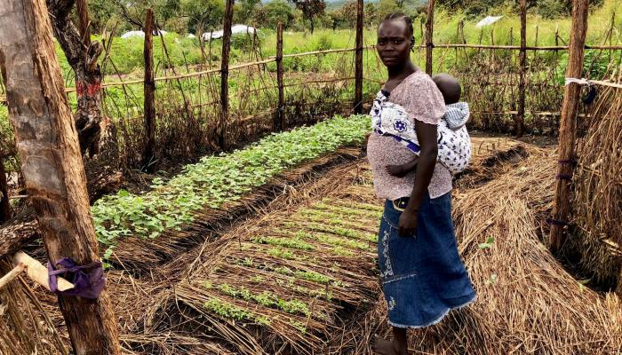 A woman with a baby on her back stands proudly in a fenced garden plot.