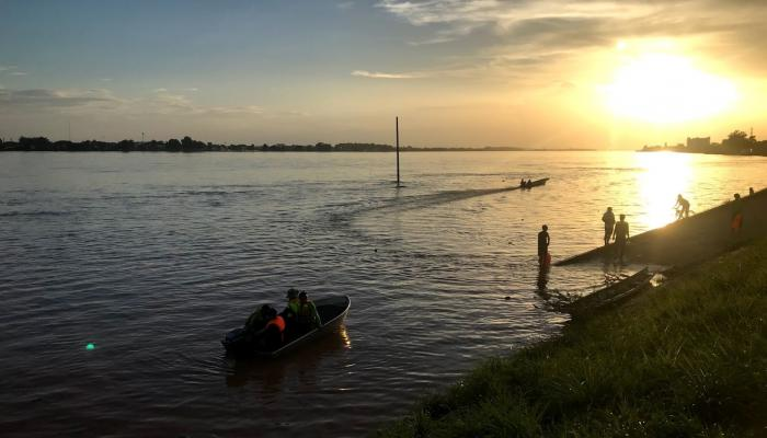 residents play and fish in the rising flood waters in Vientiane, Laos at sunset.