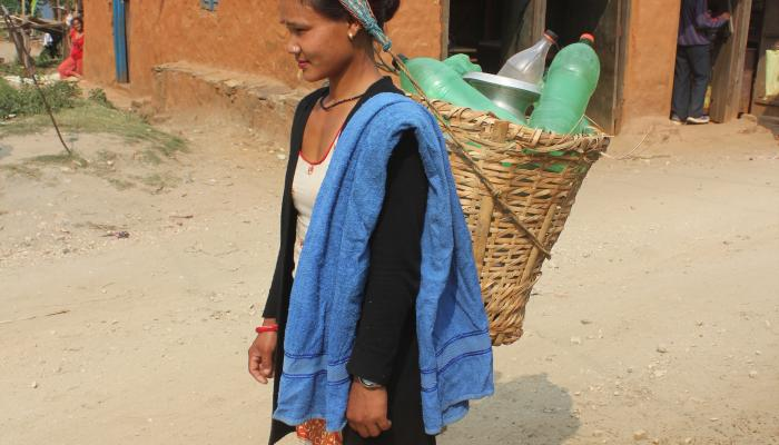 A young woman walks with heavy water jugs in a basket suspended from her back.