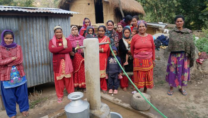 A group of women stands around a Multiple Use Water System (MUS), looking towards the photographer.