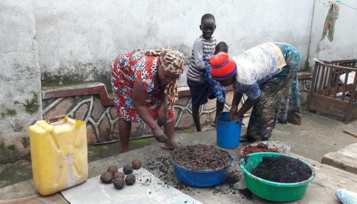 Two women make briquettes while two children sit nearby and watch.