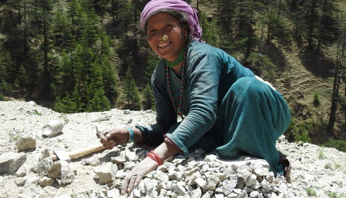 A woman kneels over a pile of stones and smiles at the camera.