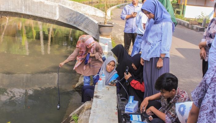 A group of students uses water quality measuring instruments near a river.