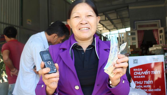 A woman holding a mobile phone in one hand and cash in the other smiles at the camera.