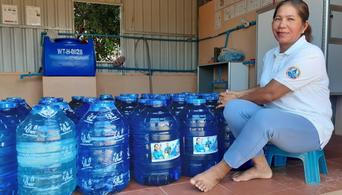A woman sits next to numerous large plastic water jugs.