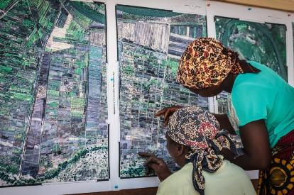 Two women face away from the camera and point at an aerial map of a village.