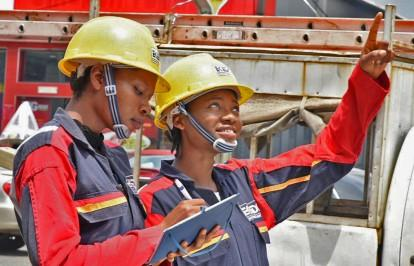 Two female line workers in uniforms and yellow hardhats stand next to each other. One takes notes while the other points upward at a power line that is out of frame.