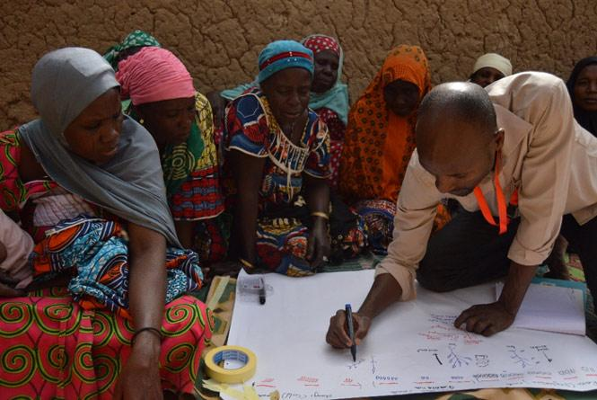 A male facilitator writes information on a poster-sized paper as a group of female farmers look on.