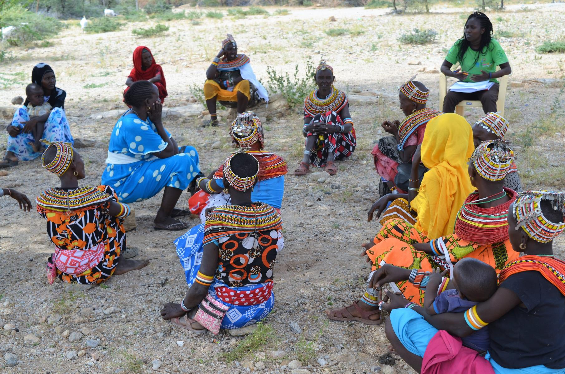 A group of women in colorful dresses sit in a loose circle and engage in discussion with each other.