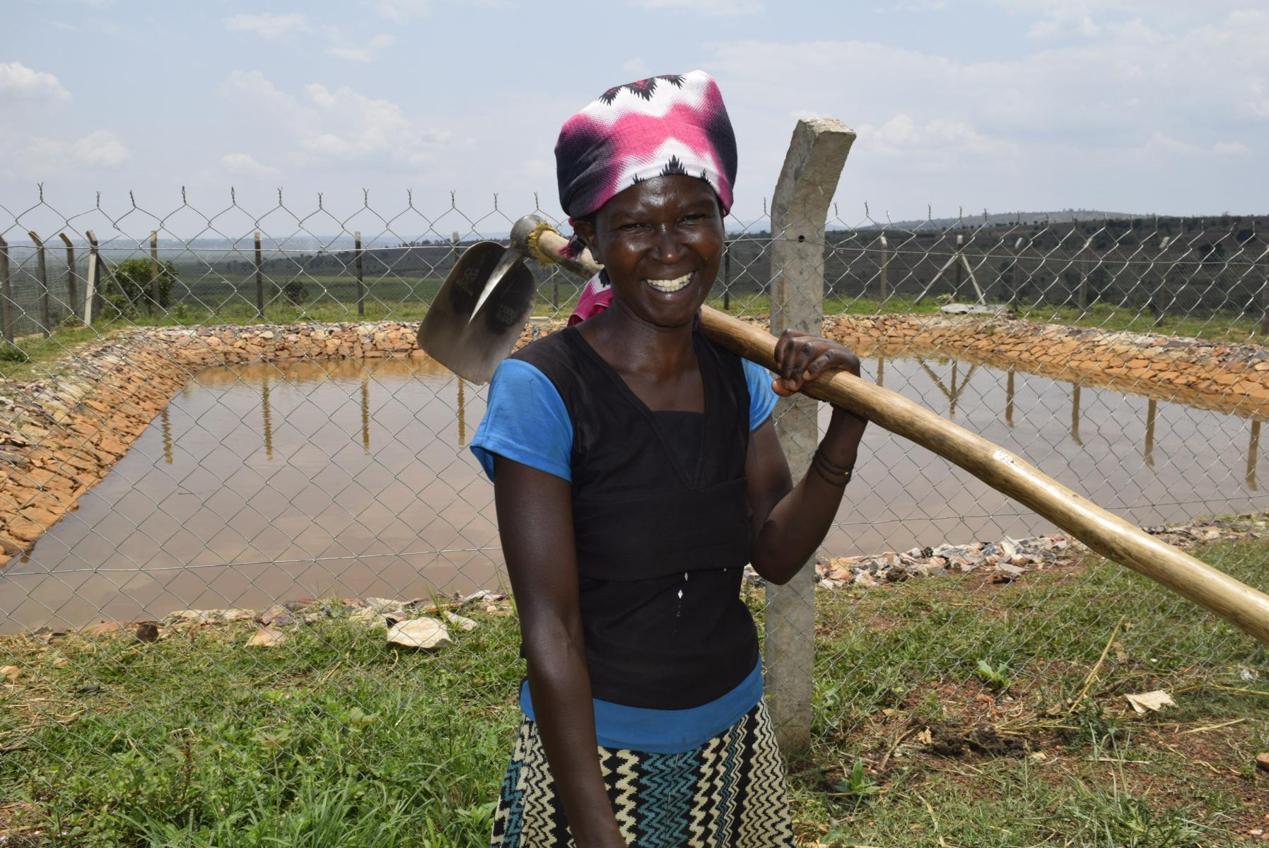 A woman holding a hoe stands in front of a fenced-in pond, smiling at the camera.