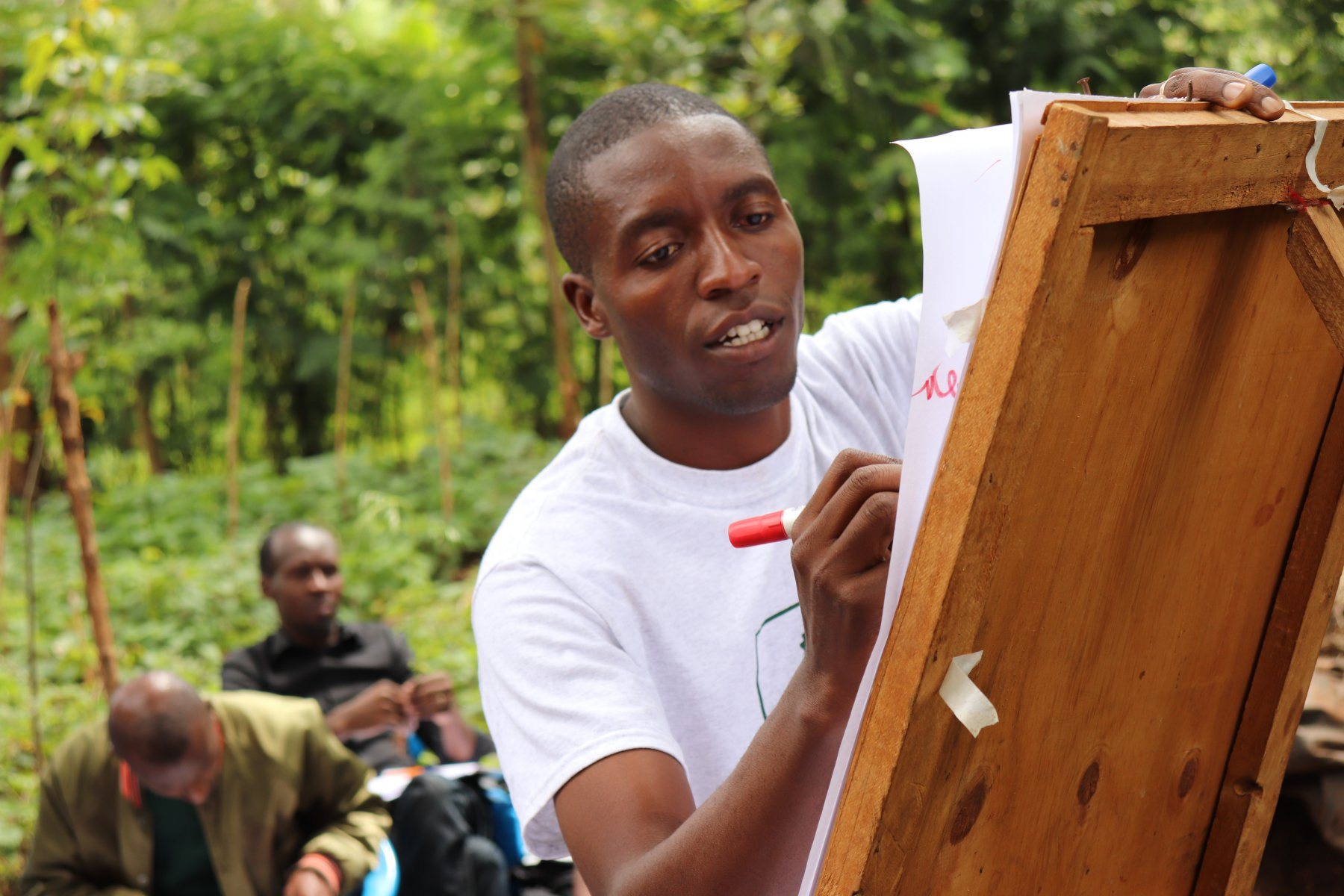 A man draws on an easel in an outdoor setting.
