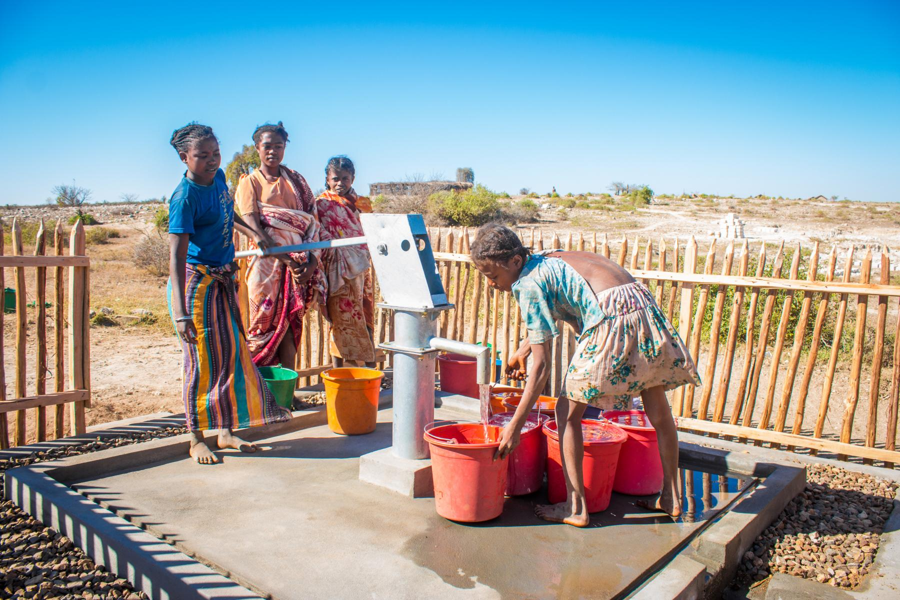 A group of women uses a water point located in an arid area.