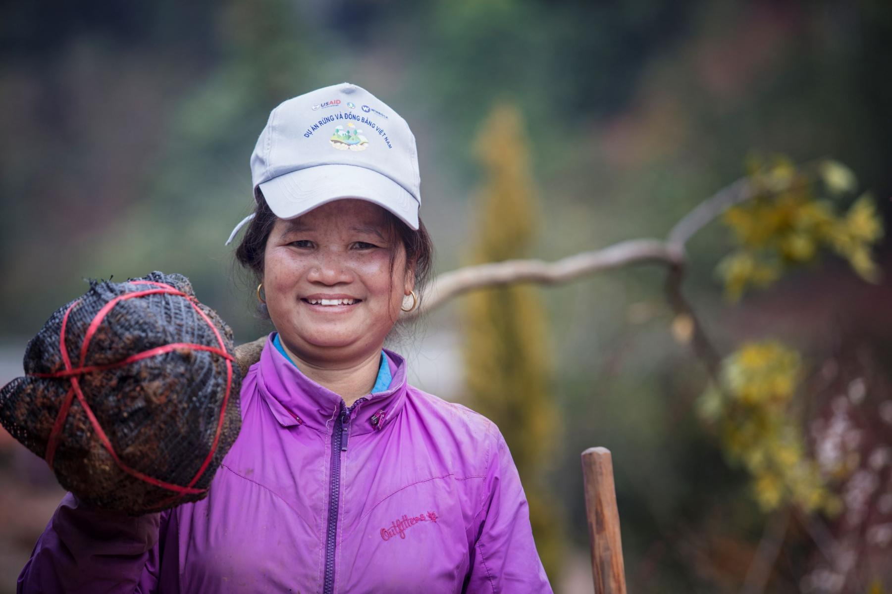 A woman with a young tree on her shoulder smiles at the camera.