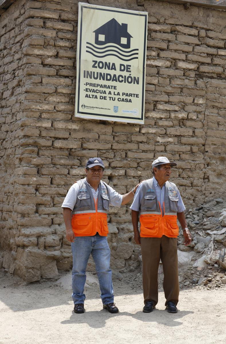Two construction workers stand in front of a flood zone sign.