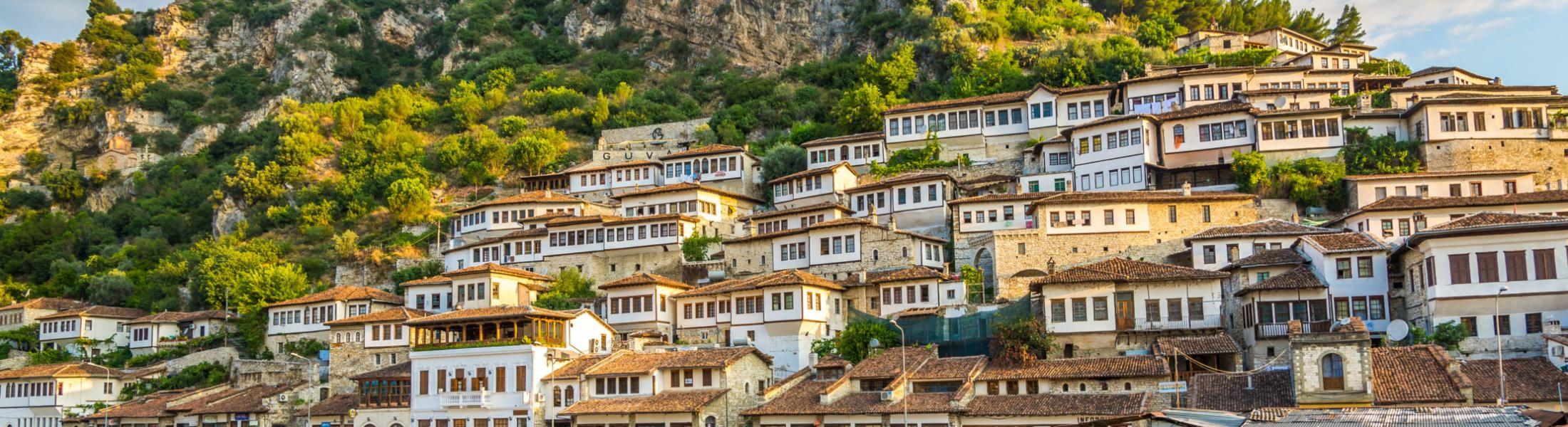 A hillside village in Albania sits next to a riverside, with a rocky hill looming over it in the background.