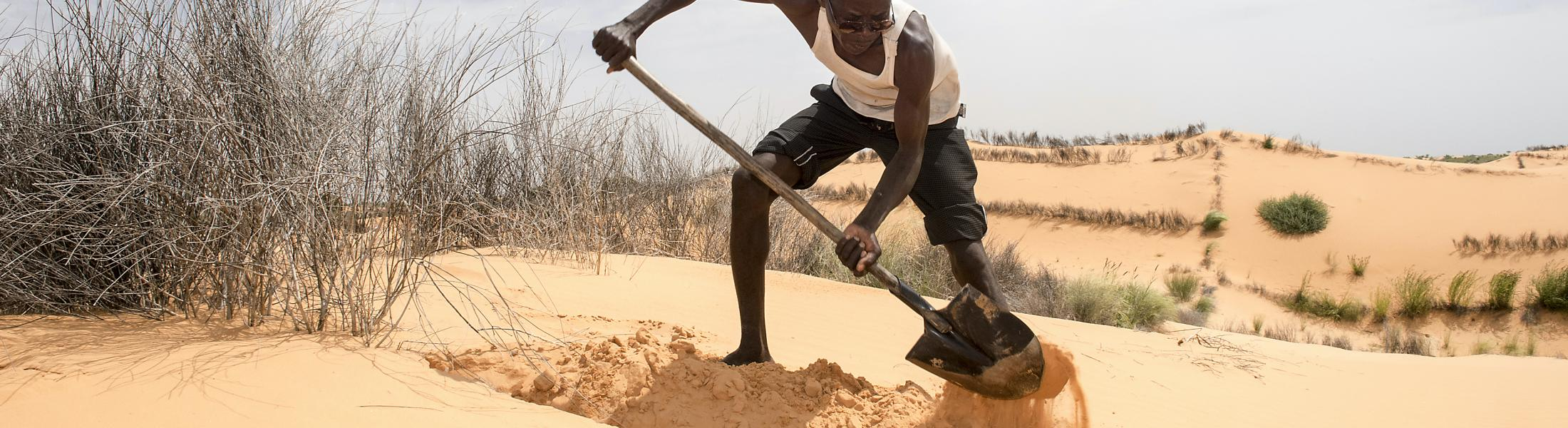 A man shovels sand in an arid environment.