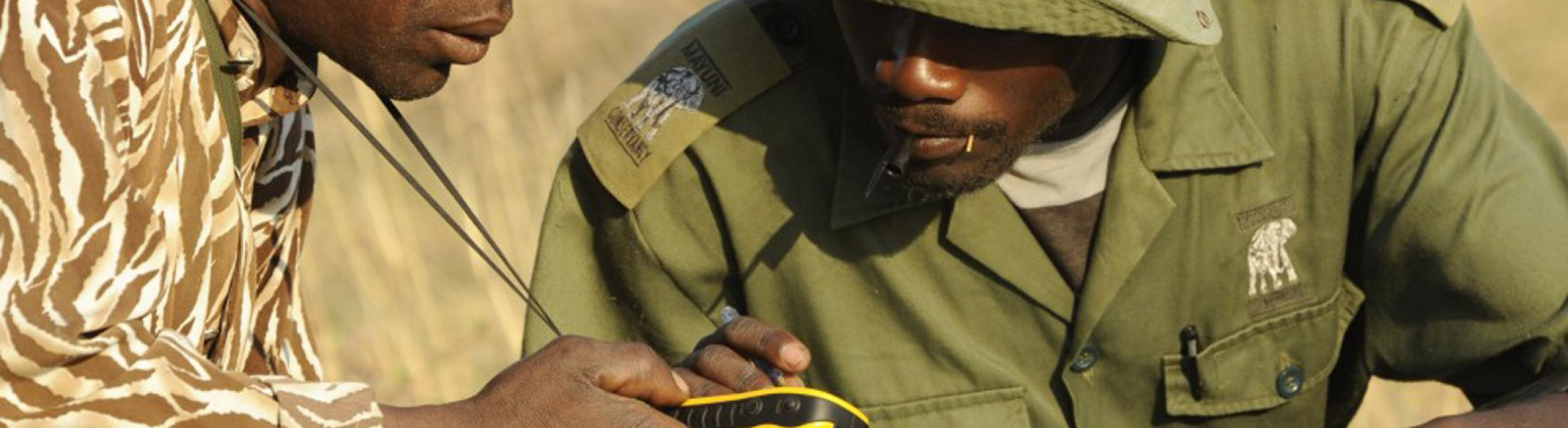 Two men look intently at a GPS unit.