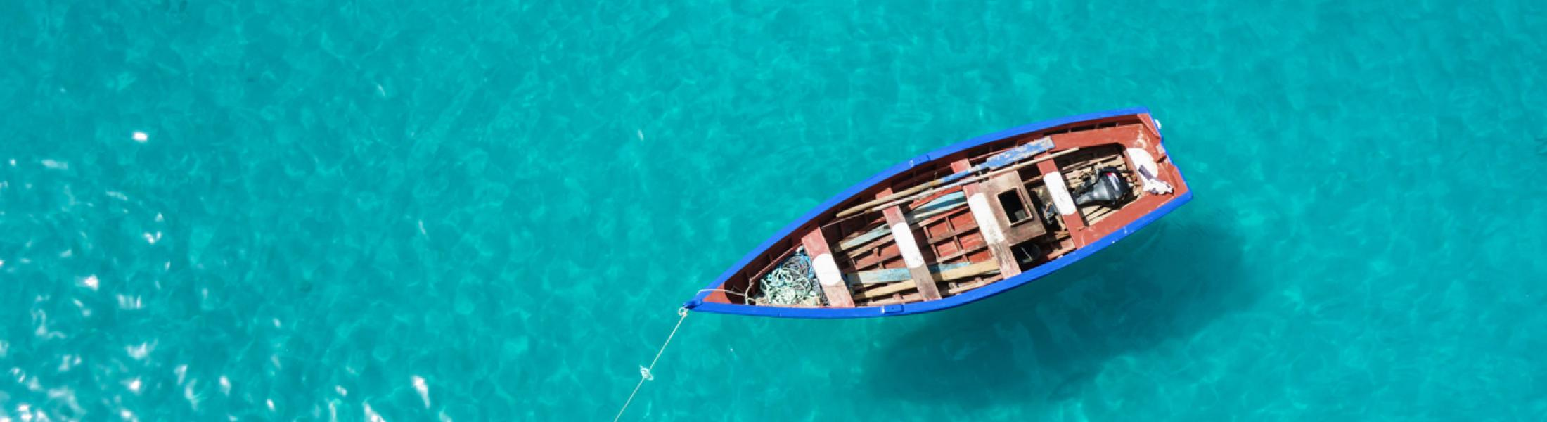 Aerial image of a small fishing boat floating in bright turquoise water.