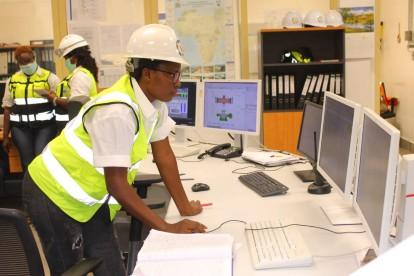 A woman in a high visibility vest and a hardhat leans on a table and looks at a bank of computer monitors.