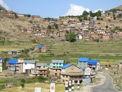 A terraced village sits above and below fields. Many of the houses have blue tin roofs that stand out against the natural tones of the landscape.