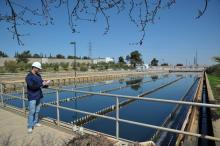 An infrastructure worker takes notes while standing near a water delivery system during an Operations and Maintenance Training Project in Jordan.
