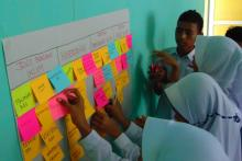 Female Indonesian students place sticky colorful sticky notes on a wall board.