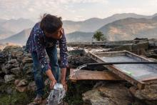 Man in Nepal fills water jug from outdoor tap.
