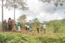 Members of Mbazzi Farmers Group members carry out a monitoring visit in their newly allocated area planted with trees.