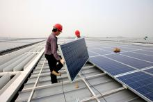 Workers install solar panels on a rail terminal, China.